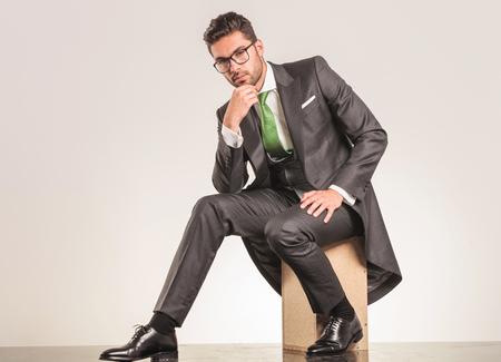 gente sentada: Hombre de negocios elegante sentado en una caja de madera, mientras que la celebración de su mano a la barbilla pensando. Foto de archivo