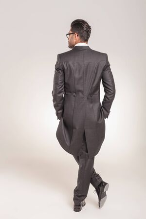 white back: Rear view of a elegant young business man standing with his hands in pockets on studio background.