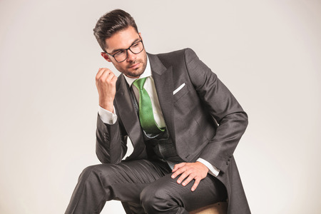 man looking down: Attractive young business man looking down while sitting on a wood box.
