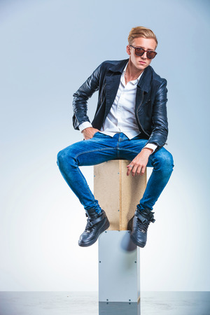 young boy holding his hand in pocket is posing while sitting on boxes with sunglasses on Stock Photo