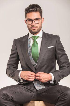 elegant business man: Elegant business man closing his jacket while sitting. Archivio Fotografico