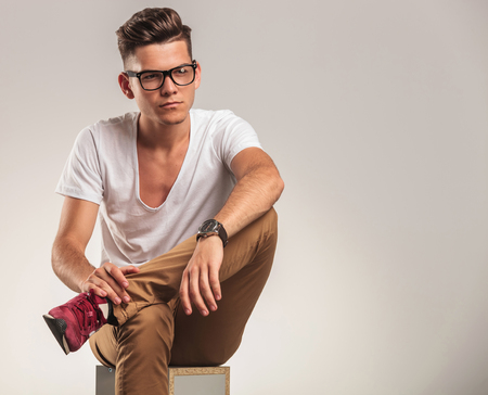 shoes off: young stylish male looking away while sitting on a chair with legs crossed