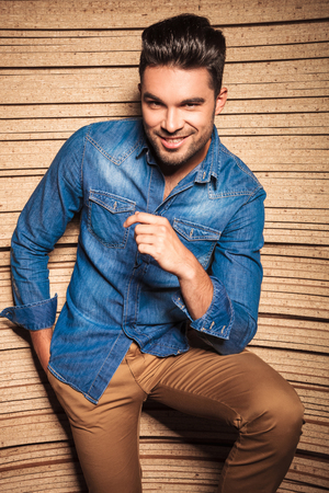 hombres jovenes: hermoso hombre sonriente mientras mantiene su mano en el bolsillo de los pantalones marrones