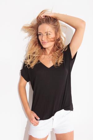 mooie blonde vrouw die haar hand in de zak van haar korte broek, terwijl het regelen van haar haar en wegkijken Stockfoto
