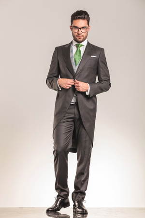 businessman suit: Young business man walking while opening his jacket, full length picture.