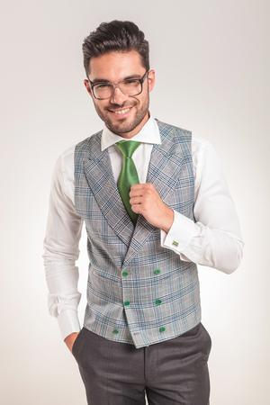 白いシャツ、グレーのベストと緑のネクタイを身に着けている若いビジネス人の映像。