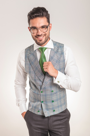 Picture of a young business man wearing a white shirt, grey vest and green tie.
