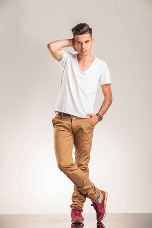 legs crossed: young man standing with legs crossed on beige studio background