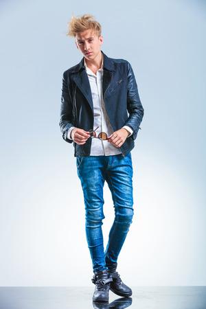 in jeans: atractiva joven rubia llevaba jeans y chaqueta de cuero mientras que la celebración de gafas de sol y mirando hacia adelante