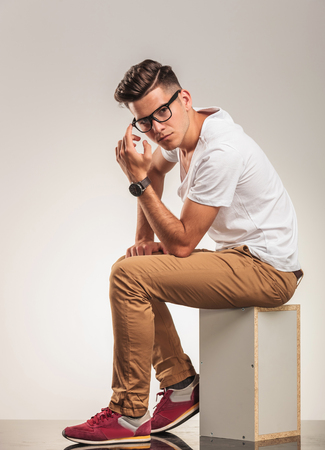 young man sitting on a chair thinking and looking at the camera Stock Photo