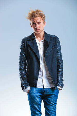 messy hairstyle: serious young man looking at the camera while holding his hands in the pockets of his blue jeans Stock Photo