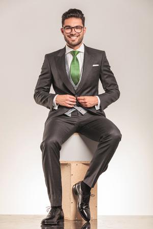 cerrando negocio: Sonriente joven hombre de negocios sentado en cajas de madera, mientras que el cierre de su chaqueta.