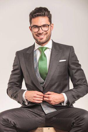 cerrando negocio: Retrato de un hombre de negocios joven sonriente cerrar su chaqueta.