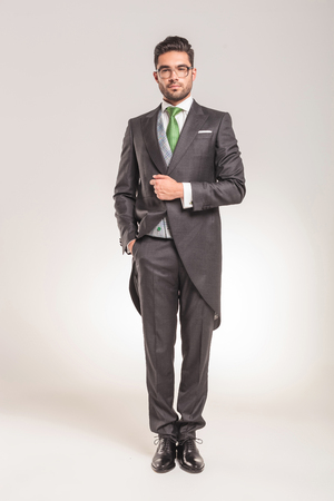 businessman suit: Full length picture of a elegant young business man standing while hoding one hand in his pocket. Stock Photo