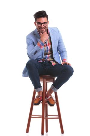 hombre sentado: El hombre de moda joven que se sienta en una silla mientras sonreía a la cámara.