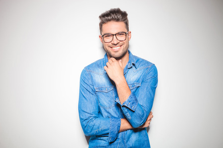 blue denim: beautiful young man wearing glasses, smiling and touching his chin Stock Photo
