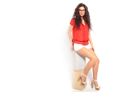 heels shoes: smart girl with curly hair wearing glasses, sitting on a chair and touching her leg while looking at the camera