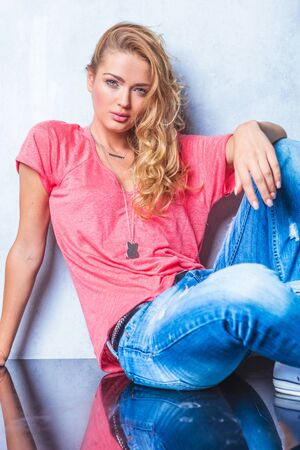 young woman sitting: close up with blonde women wearing pink shirt while posing for the camera