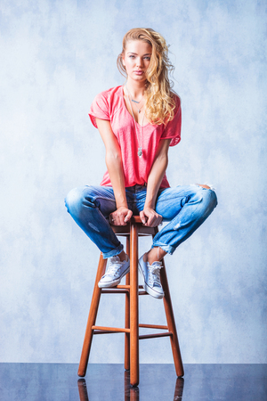 legs wide open: young attractive blonde girl posing on a chair with legs wide open Stock Photo