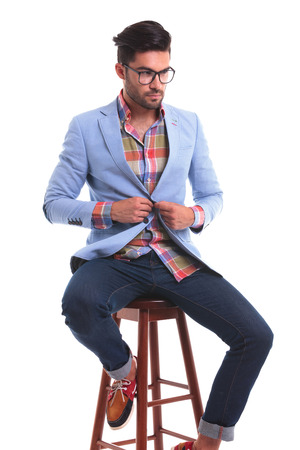 button down shirt: Young man looking down while sitting on a chair closing his jacket. Stock Photo
