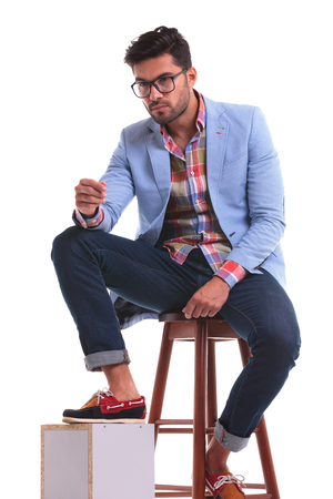 casual fashion: Attractive young man sitting on a chair while holding one leg on a wood box. Stock Photo