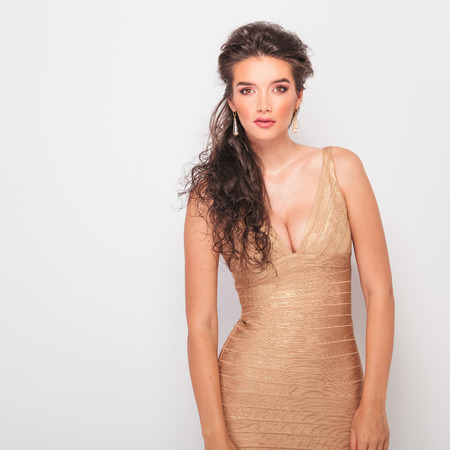 decolletage: young brunette with nice cleavage posing in studio while wearing golden dress