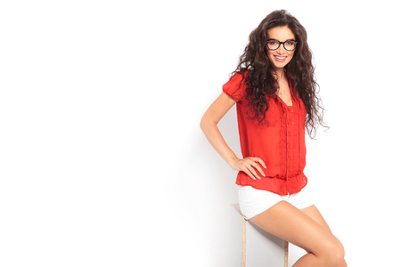 glasses model: smiling beautiful woman sitting in studio with her hand on her waist while looking at the camera