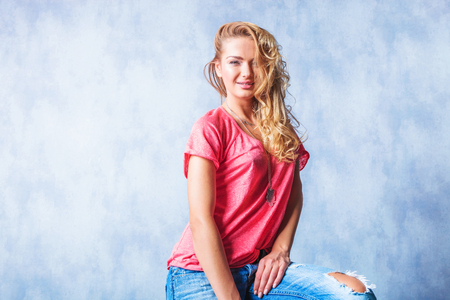messy hair: close up portrait with blonde girl smiling and sitting with rugged jeans and messy hair Stock Photo