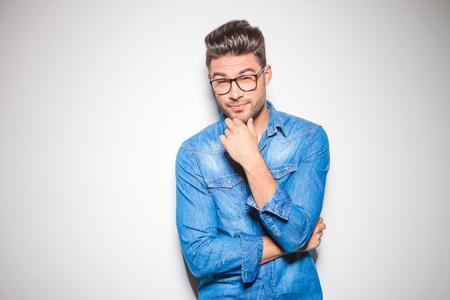 beau mec: bel homme appuyé contre le mur, toucher son menton tout en portant la chemise en jean et des lunettes
