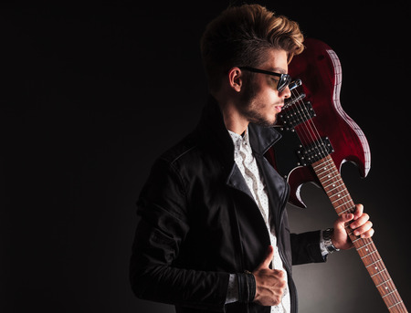 side view of a cool young guitarist holding his electric guitar on shoulder and looks down on black studio background