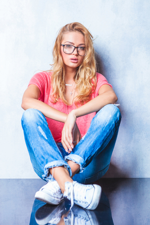shoe model: smart girl poses with glasses and mouth open while having legs crossed and hands touching