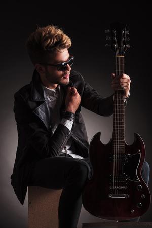 musico: vista lateral de un guitarrista sentado joven con su guitarra eléctrica y el cuello, pensando en el fondo oscuro del estudio