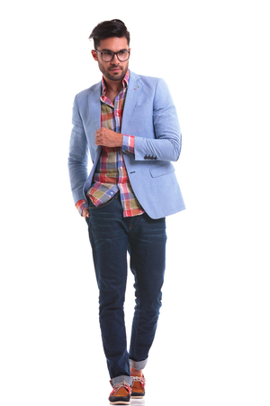 casual fashion: Attractive young man walking on isolated background with his hand in pocket.
