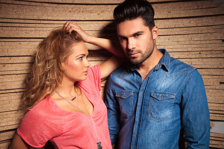 fashion: serious, young couple posing with a wood background