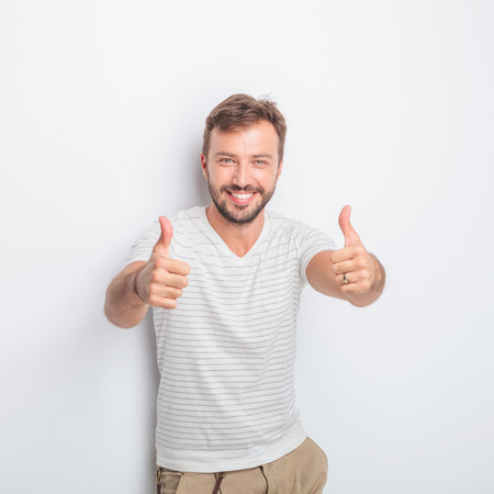 ok: happy young man making the ok thumbs up hand sign with both hands while standing in studio