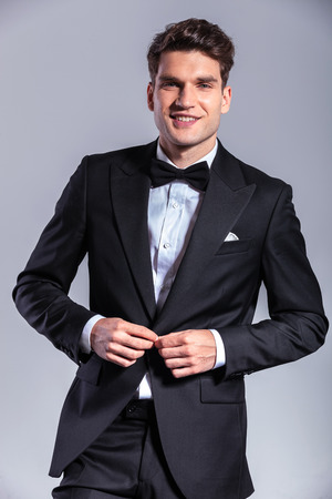 man in tuxedo: Smiling young business man unbuttoning his tuxedo with both hands.