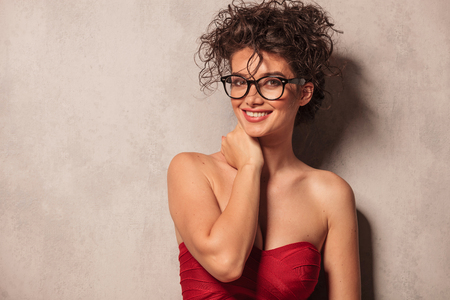 woman  glasses: portrait of a smiling elegant woman wearing a sexy red dress and glasses.