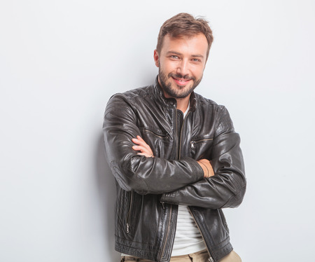 confident young man in leather jacket is standing with arms crossed against studio background Foto de archivo