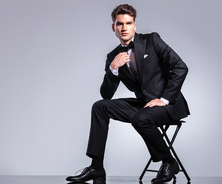 man sit: Handsome young business man fixing his bowtie while sitting on a chair.