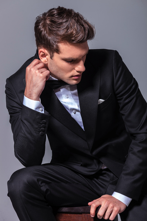 elegant business man: Elegant business man sitting on a chair while looking down.