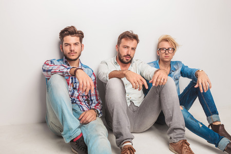 casual men: three casual men having a break and rest sitting down on the floor of the studio