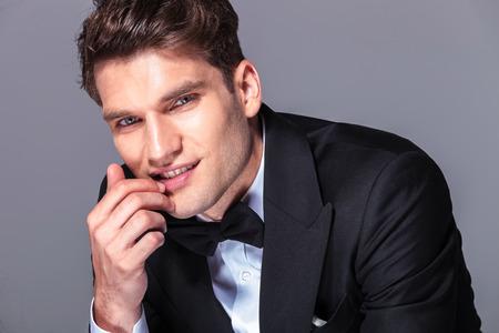 De cerca la imagen de un joven hombre de negocios la celebración de su mano cerca de la boca.