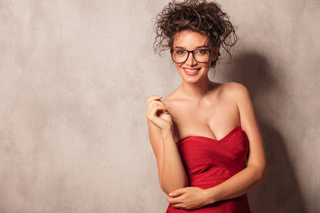 female elbow: Smiling young sexy woman holding her left hand on the elbow. Stock Photo