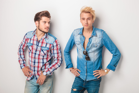 male hair: two happy young friends standing in studio, one is looking at the other