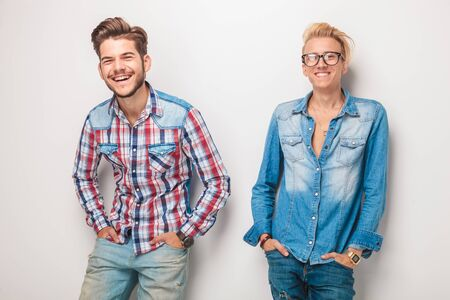standing against: two young casul men laughing together while standing with hands in pockets against studio wall