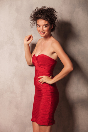 red dress: Picture of a sexy young woman posing with her hand on the waist near a grey wall.