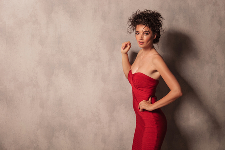 lean on hands: Side view picture of a hot young woman in a red short dress posing near a grey wall.