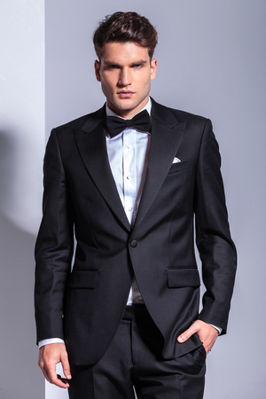 Portrait of a young business man in tuxedo holding his hand in pocket.