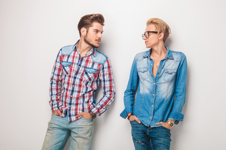 eachother: relaxed casual young men looking at eachother while standing with hands in pockets in studio Stock Photo