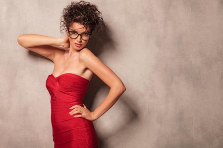 woman posing: Elegant young woman posing sexy against a grey wall.